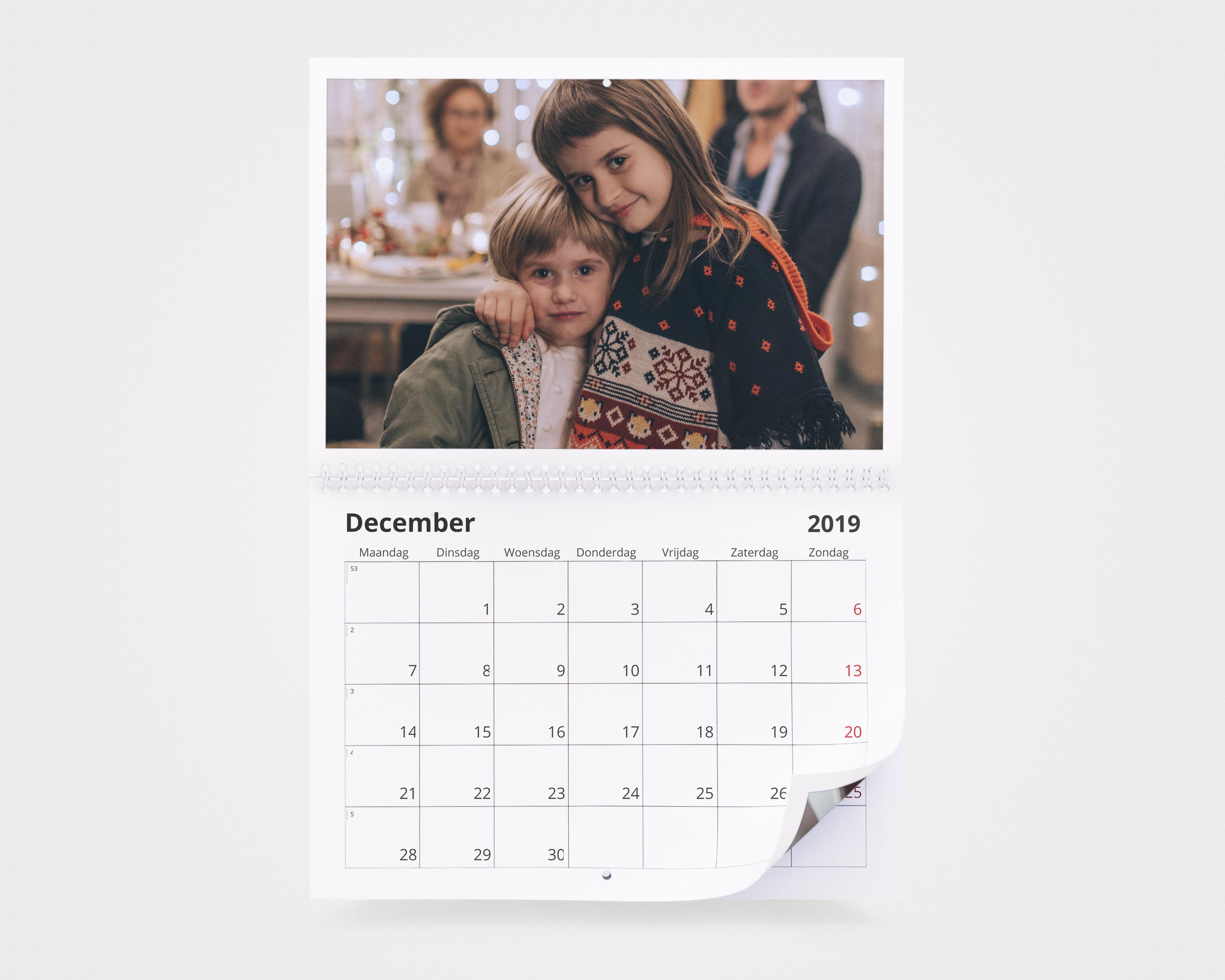 Een fotokalender met een foto van twee kinderen in kersttruien en winterjassen