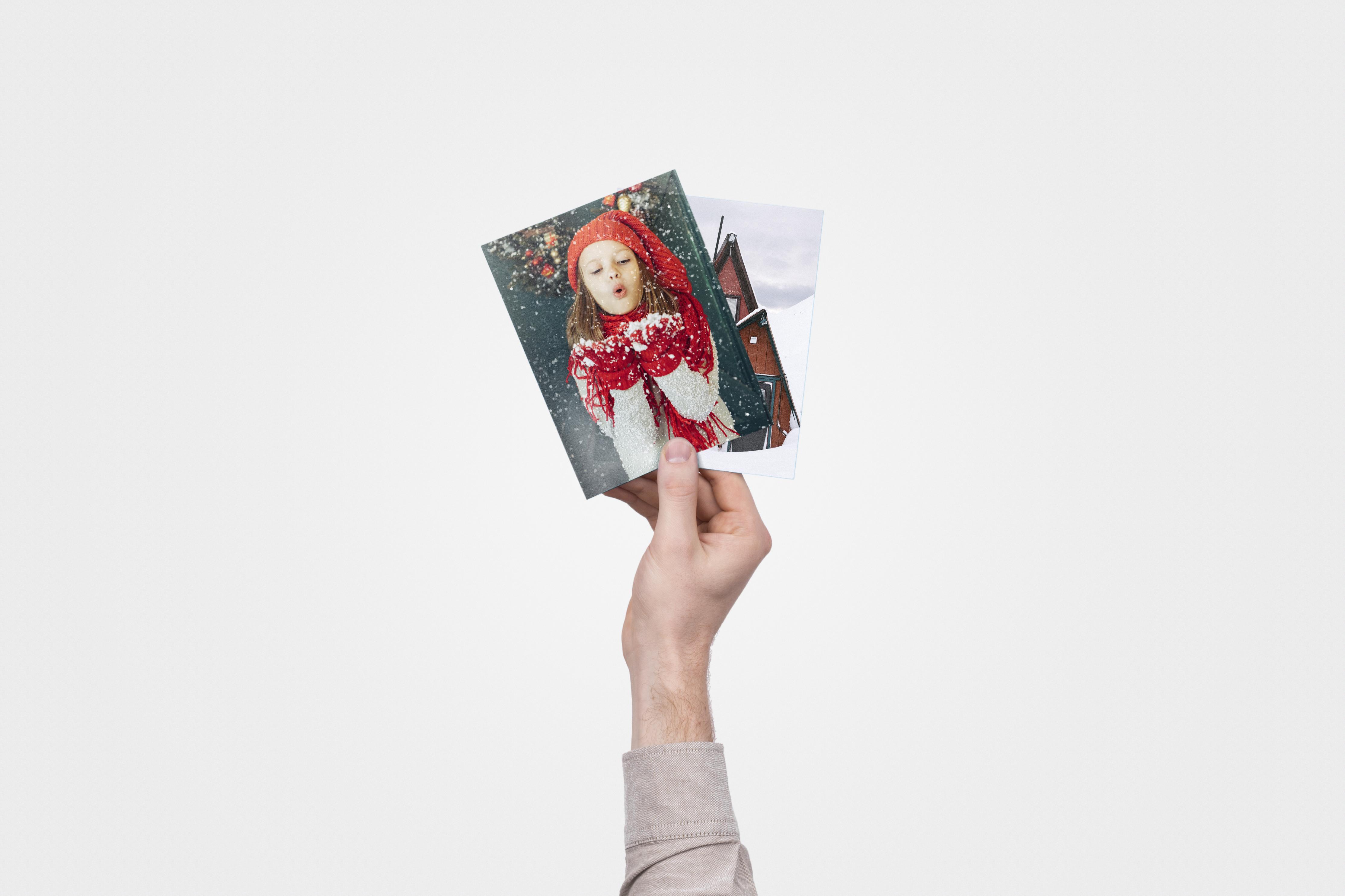 Twee winterse fotoafdrukken, één met een meisje dat in de sneeuw speelt, de andere met een huisje in de sneeuw
